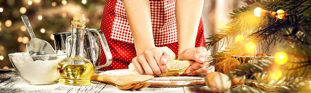 Titelbild Backen: Hände kneten einen Teig, weihnachtlich dekorierter Tisch
