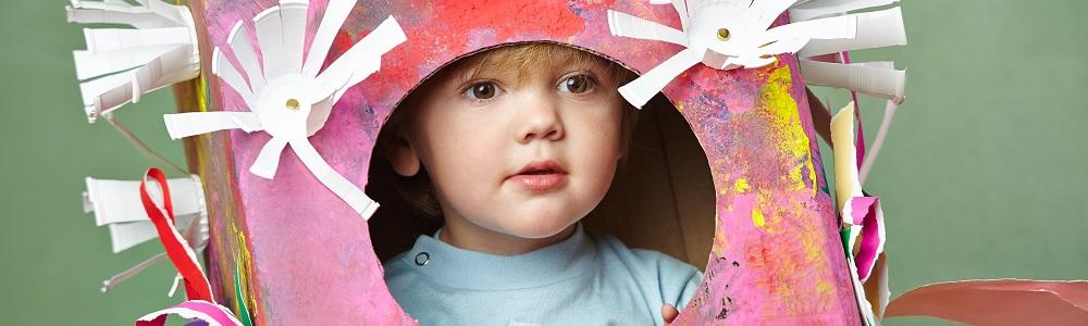 Titelbild Basteln: Kind schaut durch eine gebastelte und bemalte Box