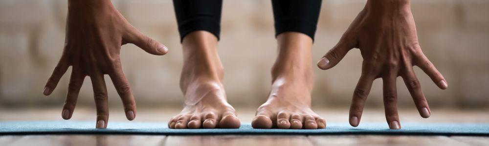 Titelbild Entspannung & Bewegung: Hände neben Füßen von stehender Person auf Gymnastikmatte