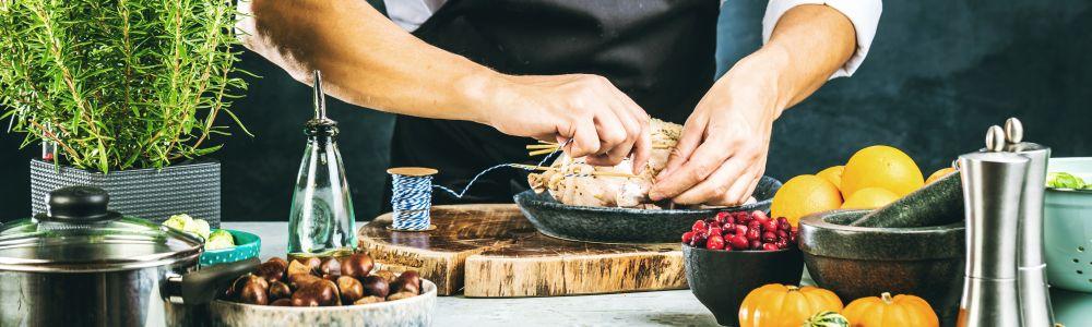 Titelbild Kochen: Hände bereiten eine Mahlzeit auf dekoriertem Tisch zu