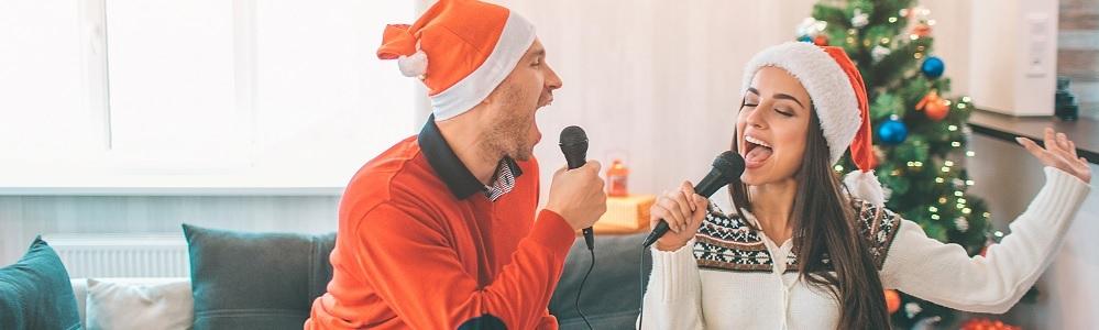 Titelbild Weihnachtslieder singen: Mann und Frau mit Weihnachtsmützen singen in Mikrofone, Weihnachtsbaum im Hintergrund