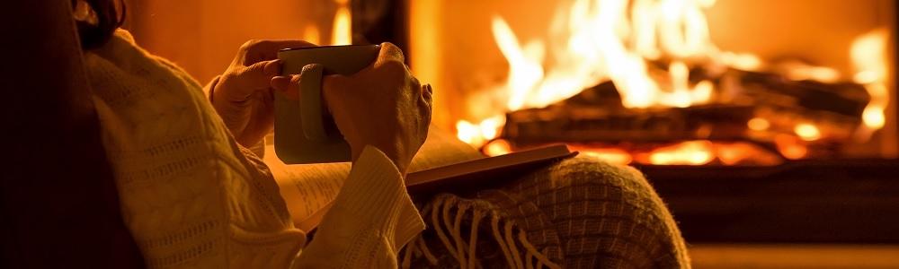 Titelbild Adventgeschichten: Mensch sitzt vor einem Kaminfeuer, Hände halten eine Tasse, Buch am Schoß